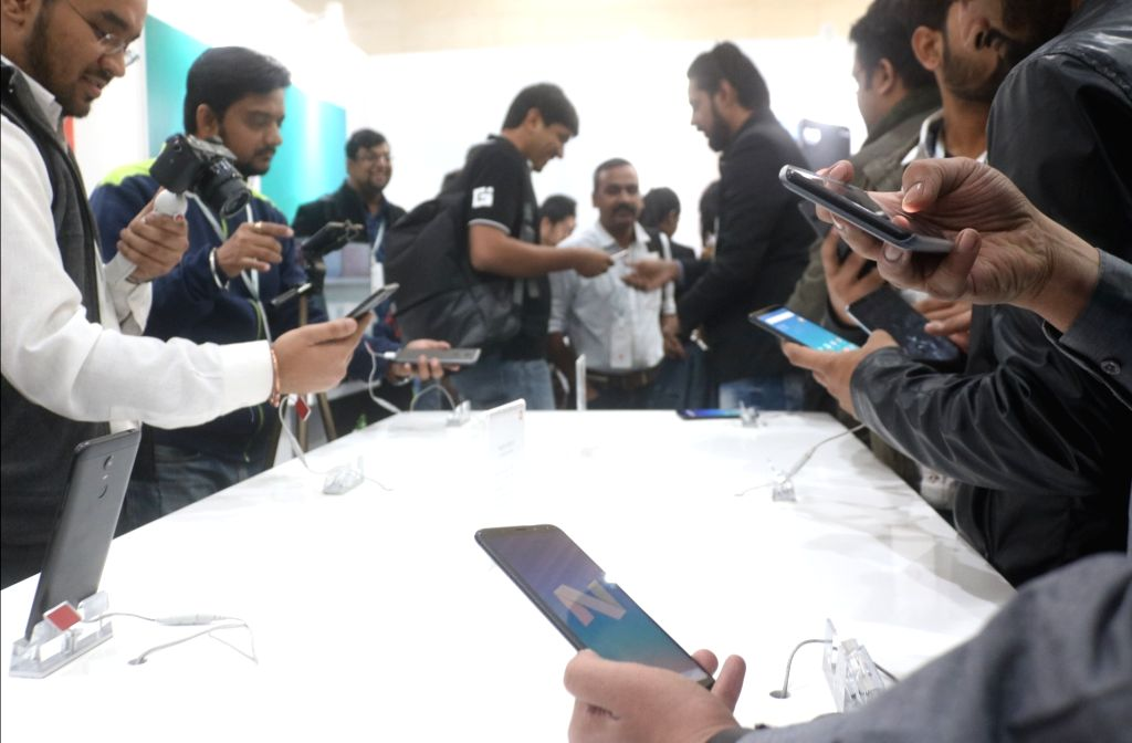 People check out the features of newly launched Xiaomi Redmi Note 5 and Note 5 Pro smartphones at a demo zone, in New Delhi on Feb 14, 2018.