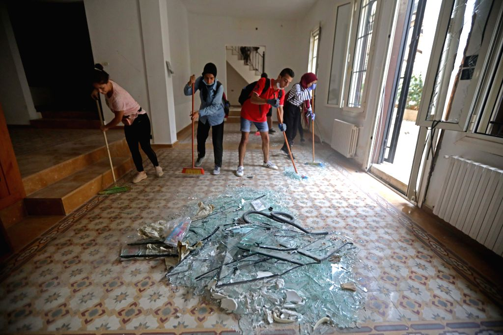People clean shattered glass in Beirut, Lebanon, Aug. 13, 2020. Beirut's governor previously announced that 300,000 people have become homeless following the ...