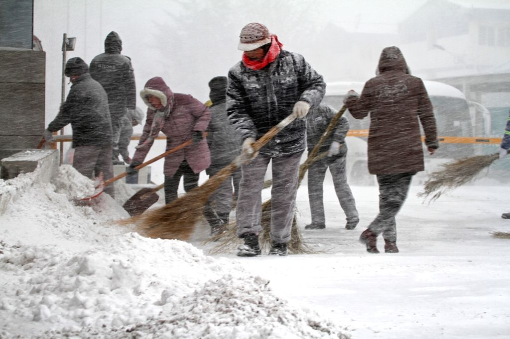 People clean the snow-covered road in Yantai, a coastal city in east China's Shandong Province, Nov. 26, 2015. A snowstorm hit the city on Thursday. (Xinhua/Tang ...
