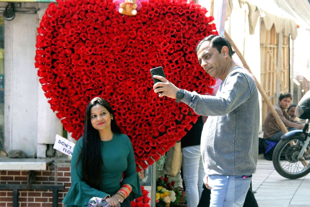 People click photos with a heart made up of roses on Valentine's Day at Connaught Place in New Delhi, on Feb 14, 2018.