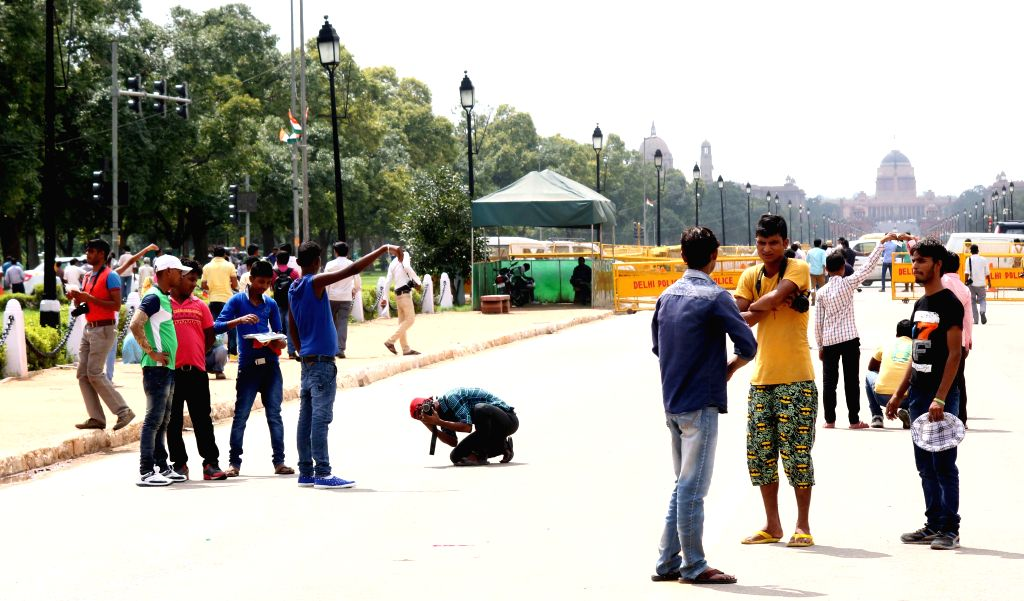 People click pictures at the India Gate in New Delhi, on Aug 19, 2015. 19th August is observed as World Photography Day across the world.