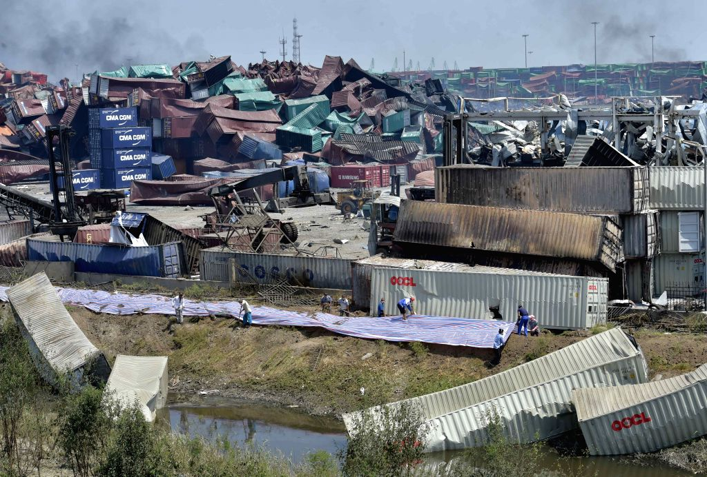 People close off the explosion site with mud and plastic in north China's Tianjin Municipality, Aug. 16, 2015. A total of 112 bodies have been found, and 95 people ...