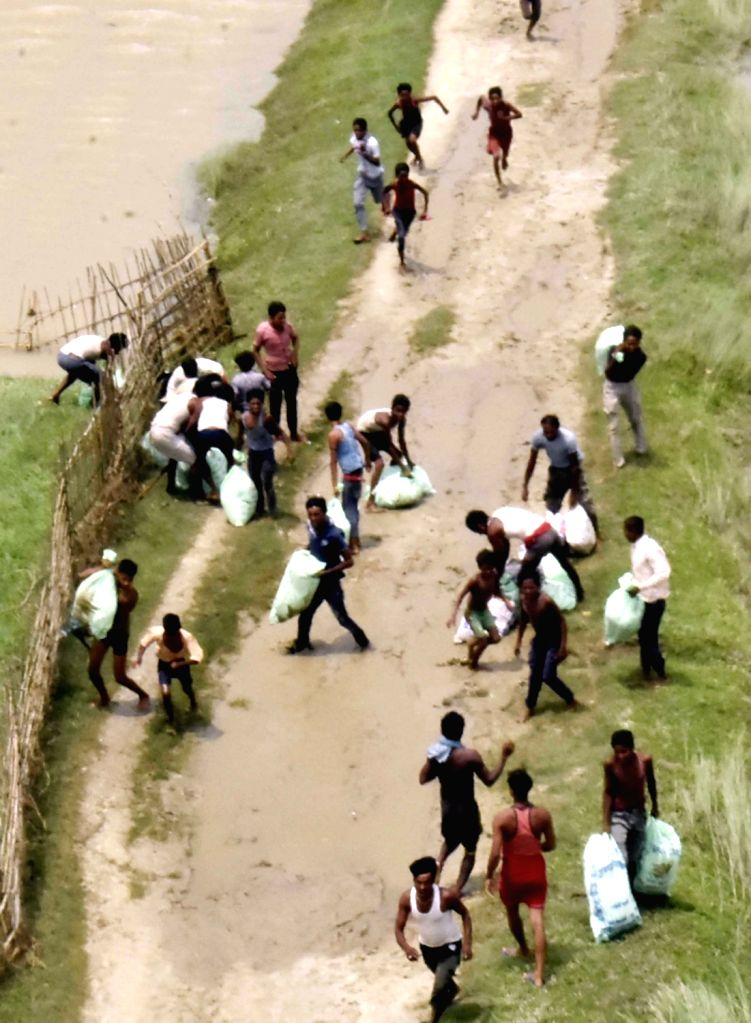 People collect the dropped food packages in Bettiah, Bihar on Aug 18, 2017.
