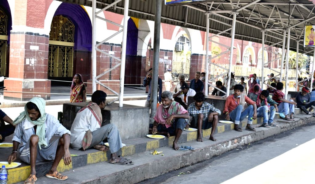 People consume food distributed among them by the Railway Protection Force (RPF) on Day 5 of the 21-day countrywide lockdown imposed to contain the spread of novel coronavirus, in Kolkata on ...