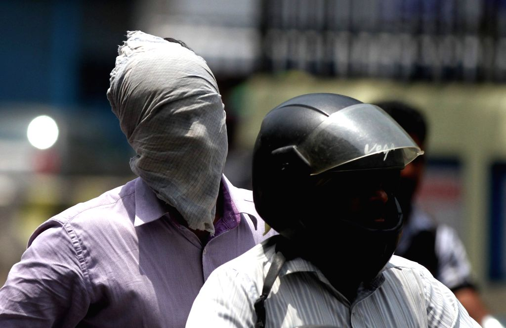 People cover their faces so as to avoid scorching sun in Chennai on May 20, 2017.