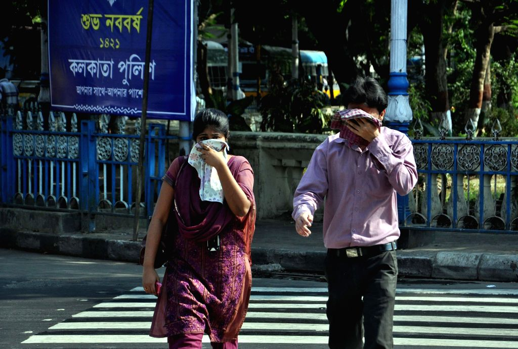 People cover themselves to avoid direct Sunlight on a hot afternoon in Kolkata on May 15, 2014.