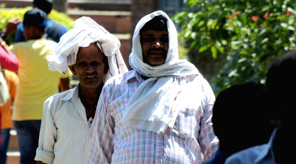 People covers themselves to avoid scorching sun on a hot day in Amritsar on May 17, 2016.
