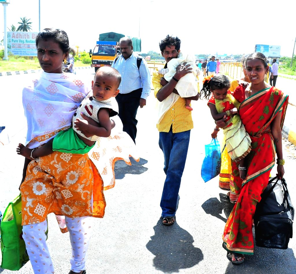 People cross Karnataka-Tamil Nadu border as vehicles were not not being allowed to enter Karnataka in the wake of protests from Pro Kannada organisation on Sept 19, 2016.