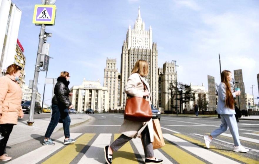 People cross the road in front of the Ministry of Foreign Affairs of Russia in Moscow, on April 16, 2021.