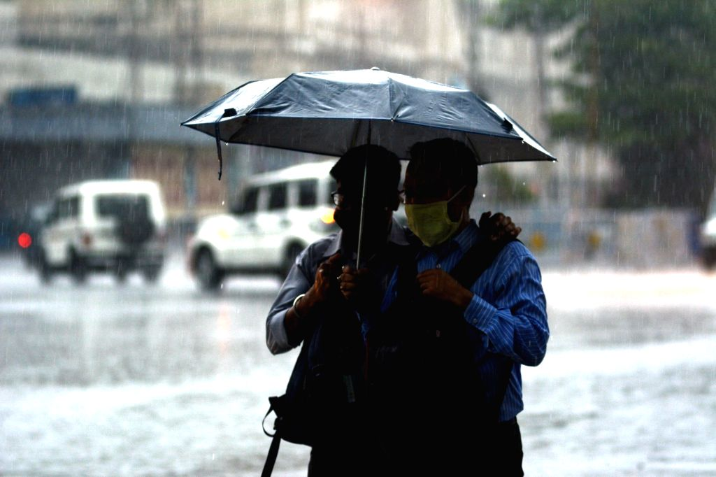 People cross the road in the rain lash in the city during the lockdown on coronavirus pandemic  in Kolkata on Monday 07 June, 2021.