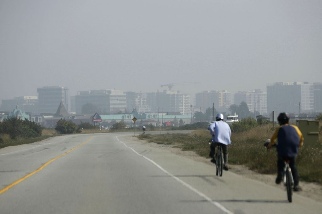 People cycle under an overcast sky caused by wildfire smoke blown up north from the US west coast in the city of Vancouver, British Columbia, Canada, Sept. 11, ...