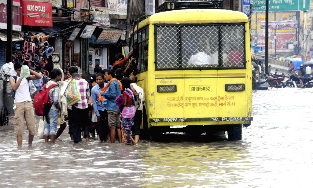 People deboard a bus on a waterlogged road of Patna on Aug 13, 2014.