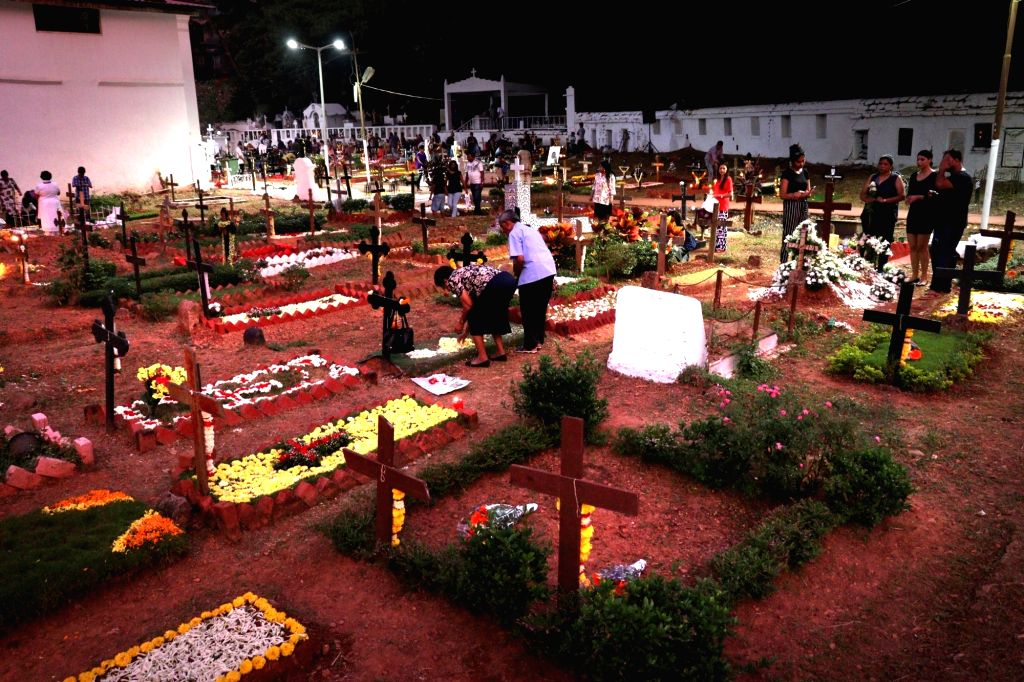 People decorating the graves of their beloved with flowers and other decorative items on the eve of All Soul Day at a cemetry near St Inez Church in Panaji on Nov. 1, 2018.