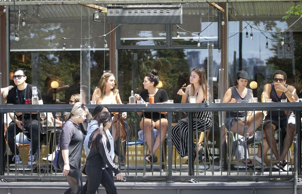People dine at a restaurant without practicing physical distancing in Vancouver, British Columbia, Canada, on July 12, 2020. In the past week, the number of new ...