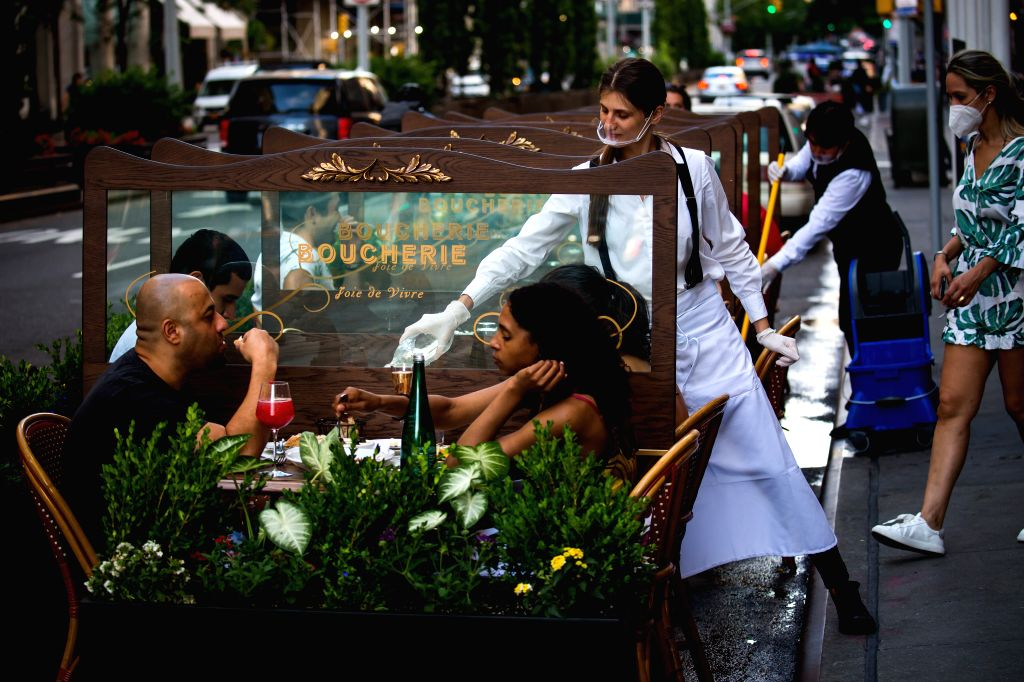 People dine outside a restaurant in New York, the United States, June 25, 2020. The number of COVID-19 cases in the United States topped 2.4 million on Thursday, ...