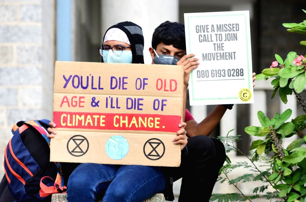 People display environment related placards in front Town Hall during the global climate strike, in Bengaluru on Sep 20, 2019.