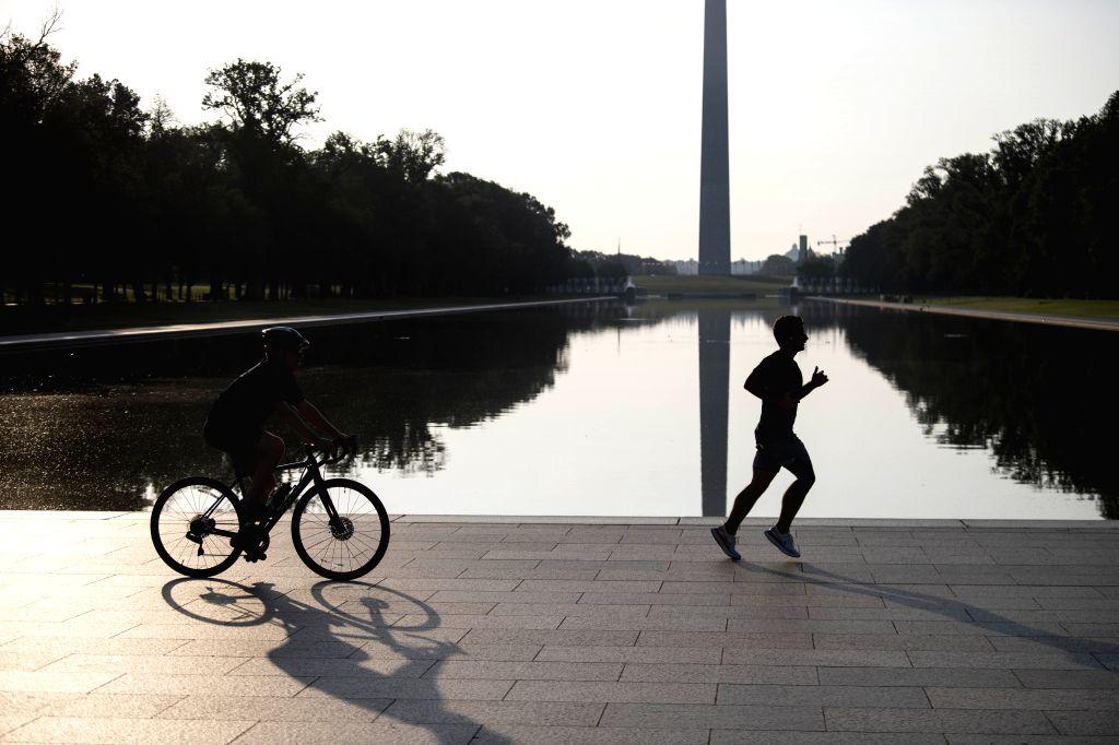 People do exercises near the Lincoln Memorial Reflecting Pool in Washington, D.C., the United States, July 8, 2020. The number of COVID-19 cases in the United ...