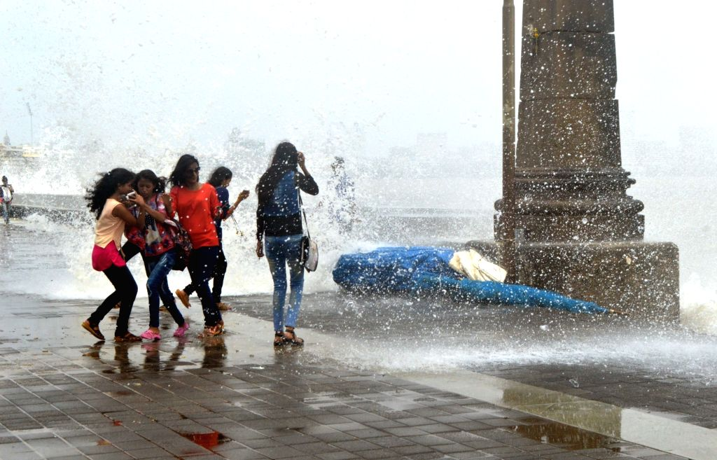 People enjoy high tide at Marine Drive in Mumbai on June 24, 2017.
