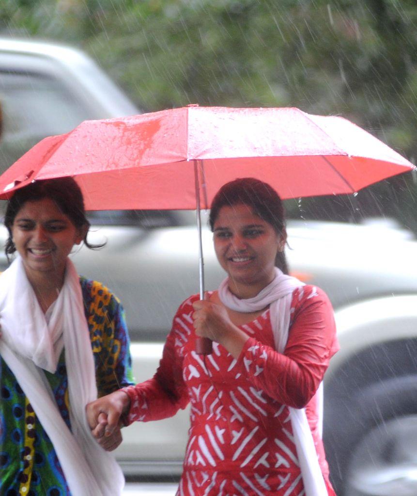 People enjoy rains in New Delhi on Aug 28, 2014.