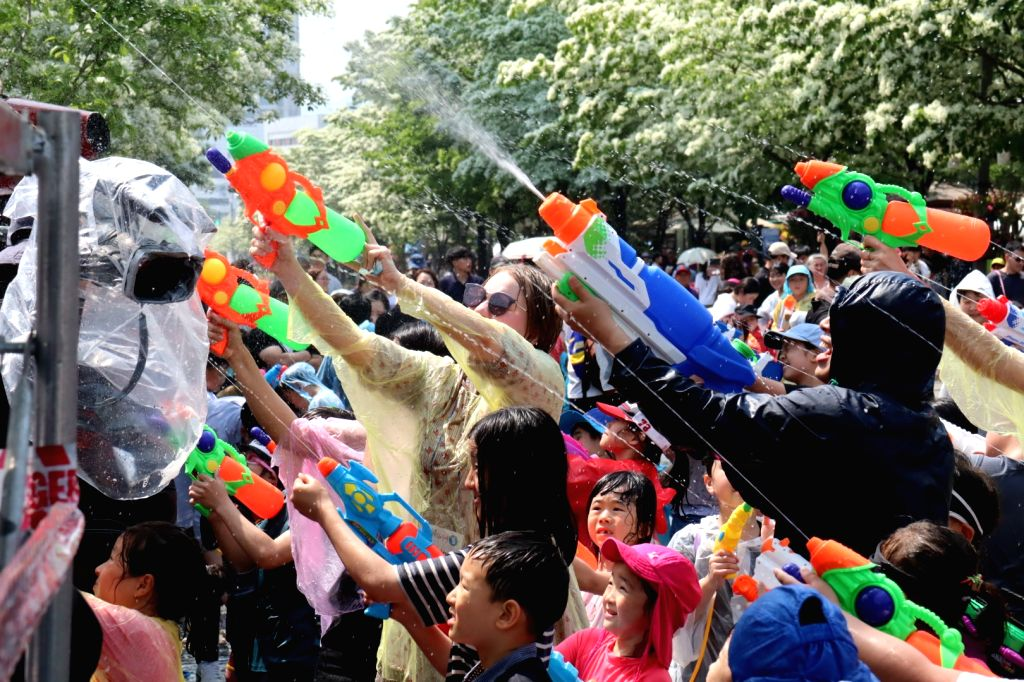People enjoy squirting water guns at Yuseong Hot Springs Culture Festival in Daejeon, 160 kilometers south of Seoul, on May 11, 2019.