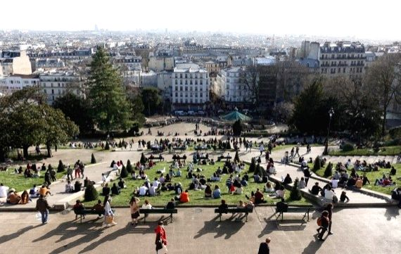 People enjoy the sunshine in front of the Sacre Coeur Basilica atop the Montmartre in Paris, France, Feb. 24, 2021.