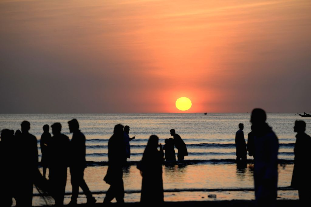People enjoy the view of sunset at a beach in southern Pakistani port city of Karachi