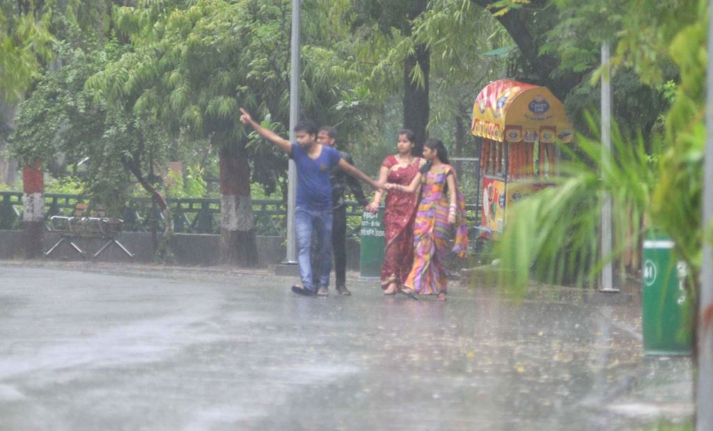 People enjoy themselves as they get drenched during rains in Lucknow on July 6, 2014.