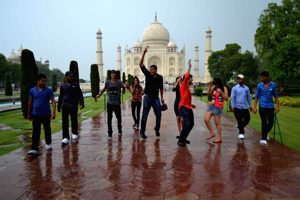 People enjoy themselves as they get drenched in rains during their visit to the Taj Mahal in Agra on July 13, 2014.