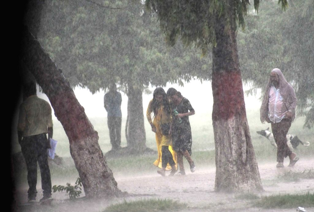 People enjoy themselves in rain at a garden in Patna on Sep 13, 2019.
