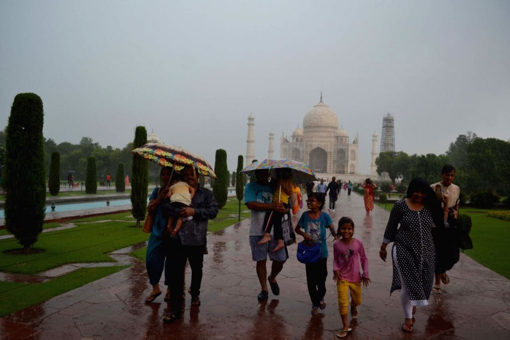 People enjoy themselves in rain at Taj Mahal in Agra on July 2, 2017.
