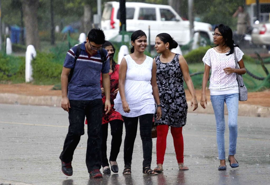 People enjoy themselves on a Delhi road during rains in the national capital on July 17, 2014.