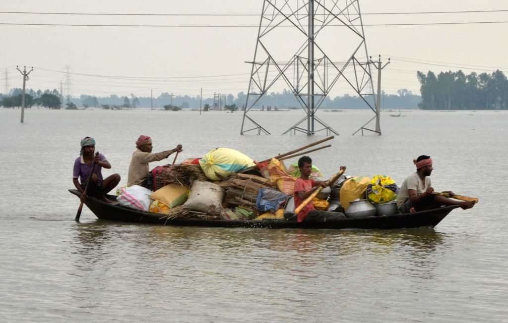 People evacuate along with their belongings using a boat in the flood hit Gazole, in Malda district of West Bengal on Aug 19, 2017.