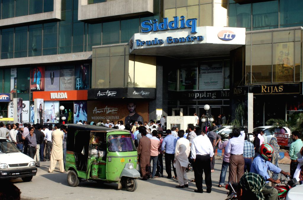 People evacuate from their offices after a severe earthquake in eastern Pakistan's Lahore on Oct. 26, 2015. At least 125 people were killed and over 1,000 others ...