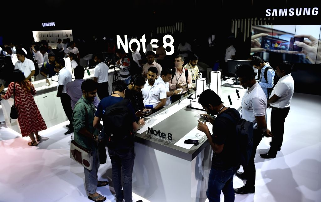 People examine the specifications of Samsung Galaxy Note8 smartphone during its launch in New Delhi on Sept 12, 2017.