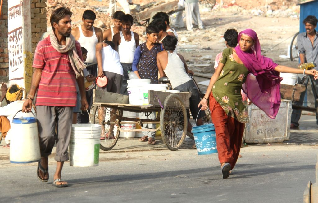 People facing water crisis since last two weeks carry potable water in Gurgaon on May 27, 2017.