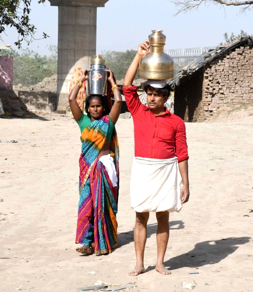 People fetch water on Day 5 of the 21-day countrywide lockdown imposed to contain the spread of novel coronavirus, in Patna on March 29, 2020.