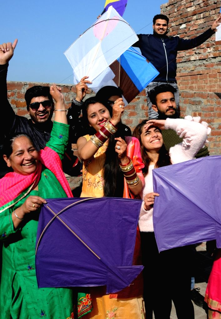 People fly kites as they celebrate Lohri festival in Amritsar, on Jan 13, 2019.