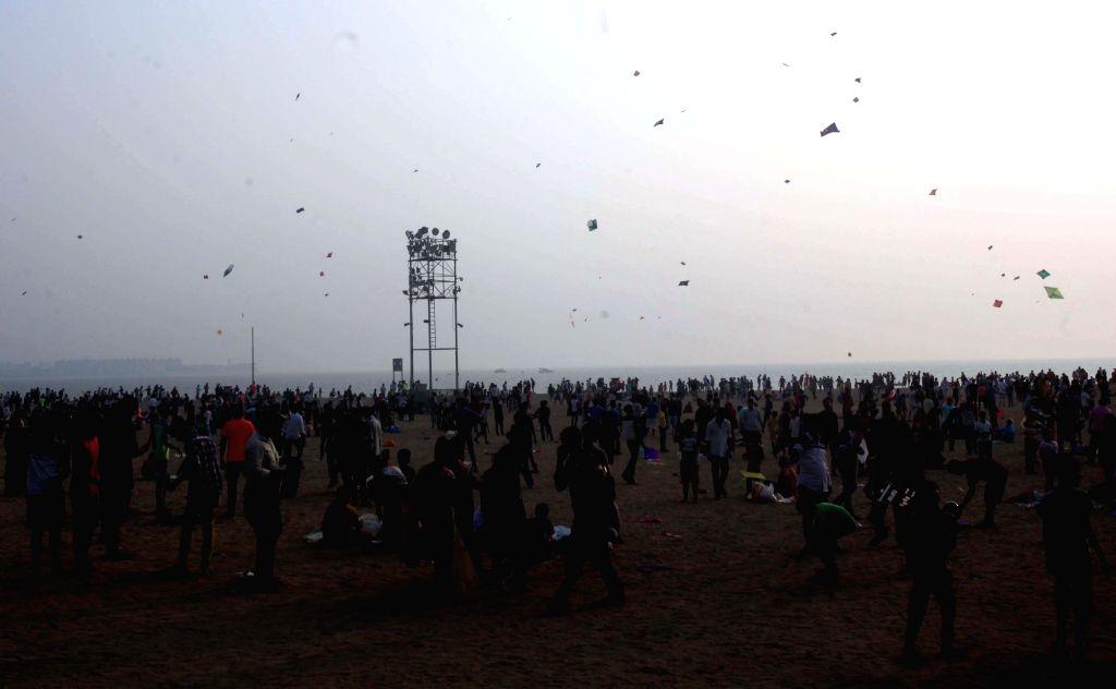 People fly kites at on the iconic beach front of Girgaum Chowpatty on Makar Sankranti in Mumbai, on Jan 14, 2017.