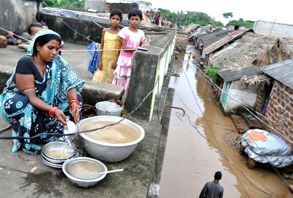 People forced to live on their roof tops in flood affected Kakharubasta village of Odisha on Aug 8, 2014.