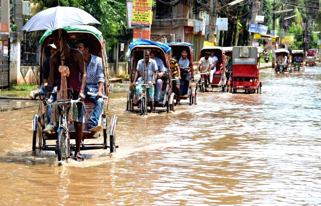 People forced to take rickshaw as roads get flooded after heavy showers in Guwahati on Aug 8, 2014.