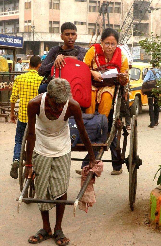 People forced to take rickshaws as taxi drivers go on strike in Kolkata on Aug 7, 2014.