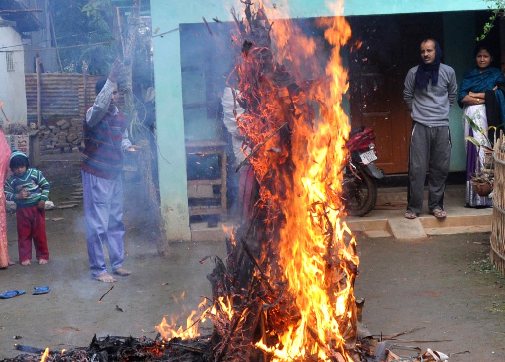 People from Assamese Community enjoys the Magh Bihu by burning the Holy Meji on the day of Magh Bihu in Guwahati, on Jan 16, 2016.