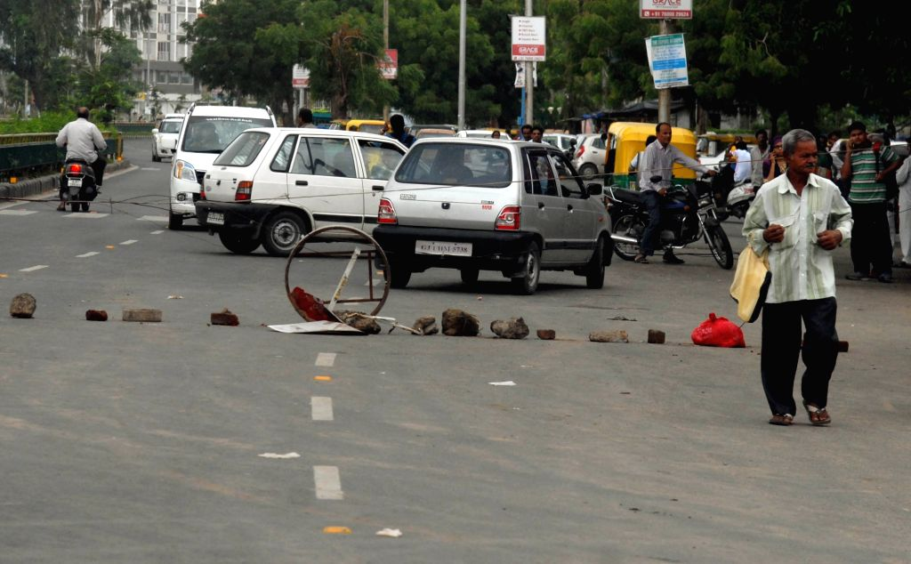 People from Dalit community block traffic after four men belonging to the Dalit community were beaten while trying to skin a dead cow at Una village; in Ahmedabad on July 20, 2016.