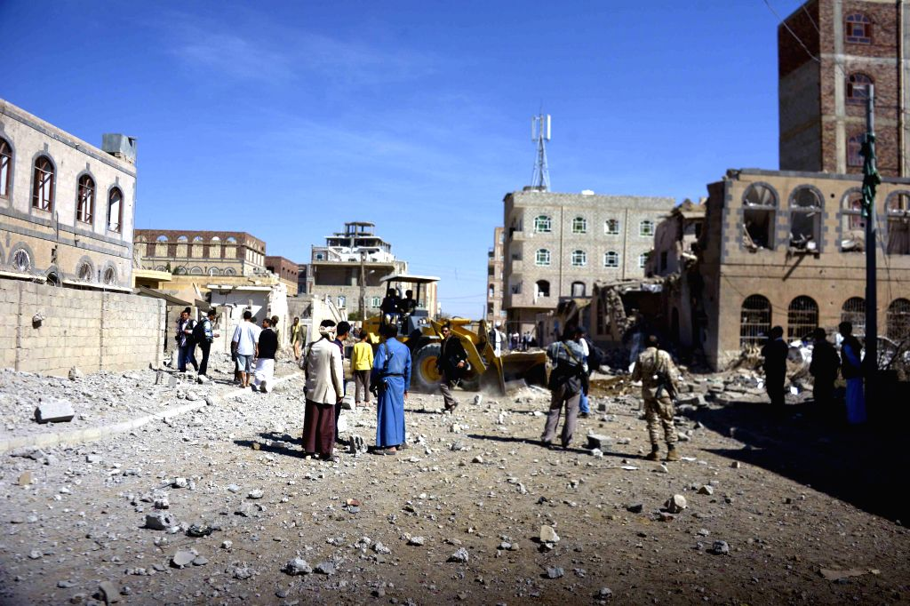 People gather around at a building destroyed in airstrikes of the Saudi-led coalition that wounded at least six people in Sanaa, Yemen, on Oct. 28, 2015. The ...