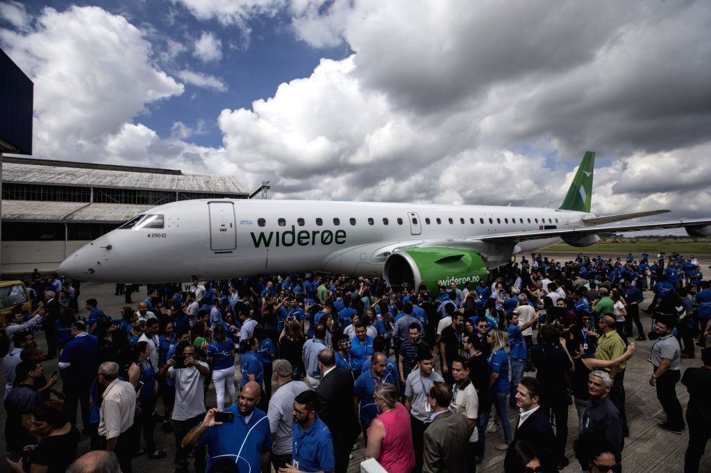 People gather around the E190-E2 jet after the delivery ceremony of Embraer's first E190-E2 jet at its headquarters in Sao Jose dos Campos, Brazil, on ...