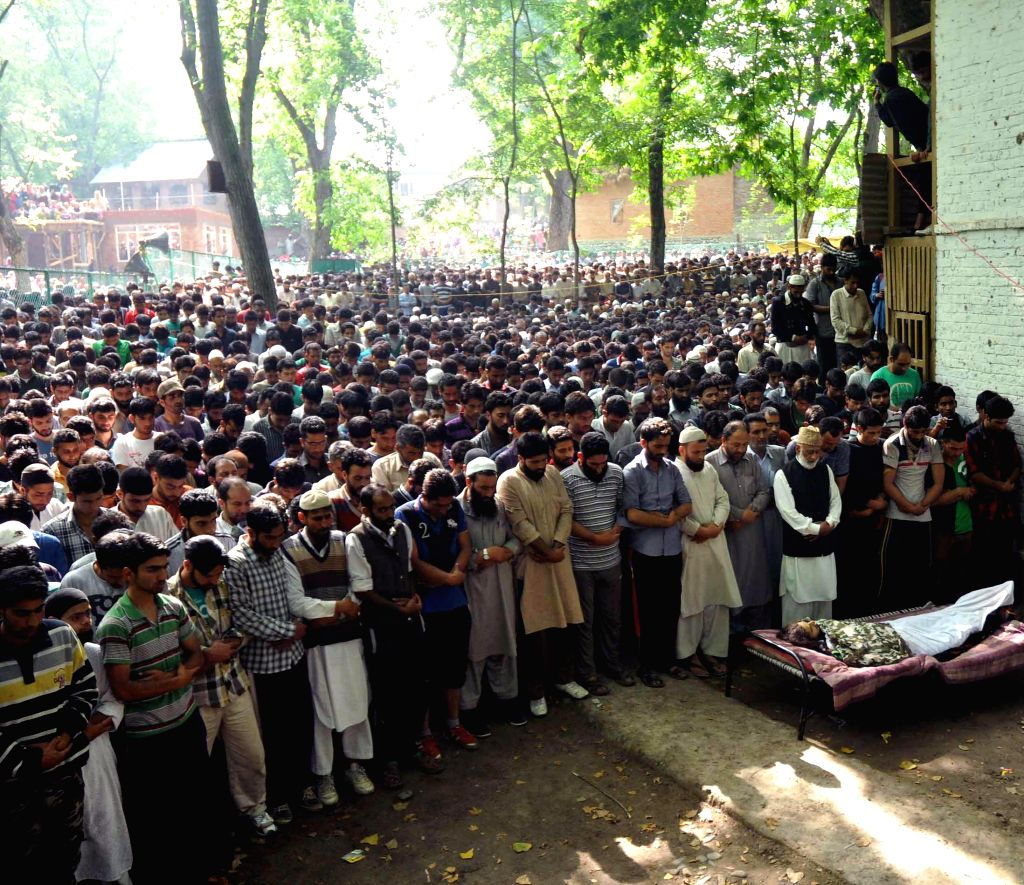People gather at the funeral of the three extremists who were killed on 19th June in a gunfight with the security forces in Pulwama district of Jammu and Kashmir, on June 20, 2014.