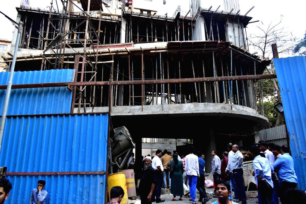 People gather at the site where a portion of a slab of an under-construction building collapsed in Mumbai's Nagpada, on April 15, 2019.