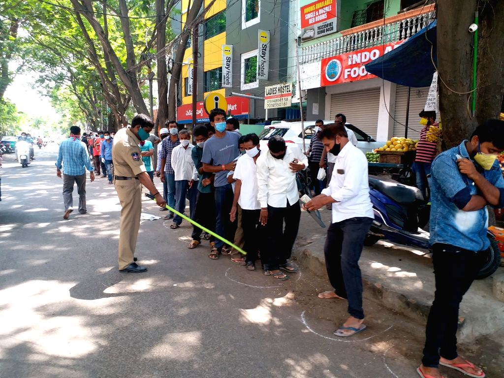 People gather in long queues to purchase liquor at a wine and beer shop at Hyderabad's Banjara Hills during the extended nationwide lockdown imposed to mitigate the spread of coronavirus, ...