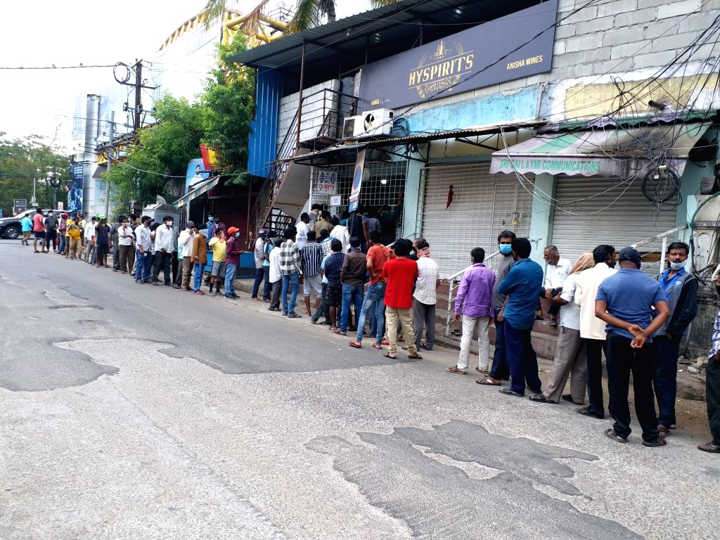 People gather in long queues to purchase liquor at a wine and beer shop in Hyderabad during the extended nationwide lockdown imposed to mitigate the spread of coronavirus, on May 6, 2020.