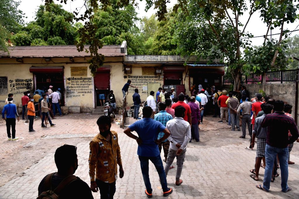 People gather in long queues to purchase liquor outside a wine and beer shop in East Delhi's Kalyanpuri during the extended nationwide lockdown imposed to mitigate the spread of ...